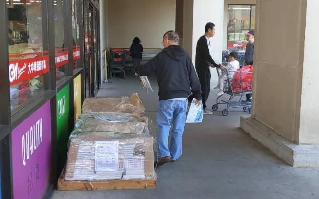 民眾在大中華超市門口,拿著電話簿翻看。(記者蕭永群/攝影)
