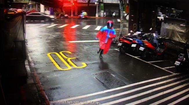 縱火嫌犯身穿紅色雨衣,頭戴安全帽企圖影響警方追查。(記者蔡翼謙/翻攝)
