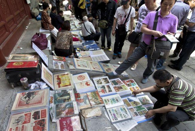 收藏愛好者在北京報國寺收藏市場觀看票據藏品。(新華社資料照片)