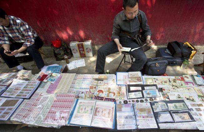 票據收藏者在北京報國寺收藏市場整理藏品。(新華社資料照片)