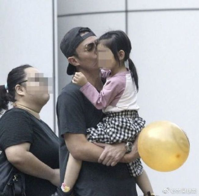 霍建華抱著女兒小海豚出遊,慈愛地親吻愛女。(取材自微博)