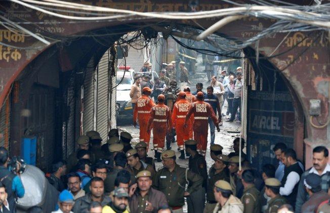 印度首都新德里一家工廠8日發生火災,消防員趕往現場救火。(路透)