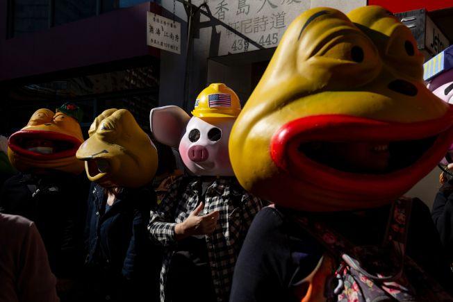 香港8日大遊行中,有民眾戴著「連登豬」(中)和「佩佩蛙」(反送中蛙)的頭套,兩者皆是反送中示威者用來表達抗爭訴求的象徵。(Getty Images)