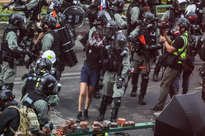 過去半年警方共拘捕近5980人,當中學生累積逾2380人。圖為11月18日警察在理大拘捕一名示威者。(Getty Images)