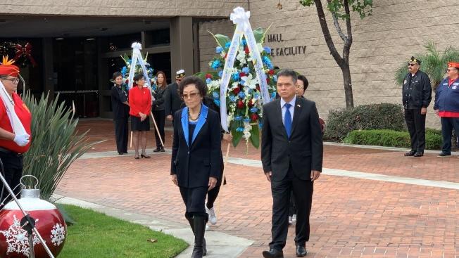 中國駐洛杉磯總領館僑務領事何明(右)和中國大陸僑團巾幗會會長張素久為死難者敬獻花圈。(記者王子銘/攝影)
