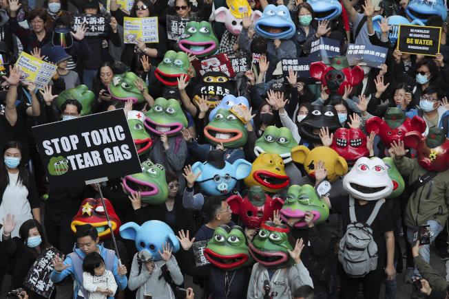 在6月9日香港反送中運動首場百萬人大遊行屆半年之際,香港民間人權陣線8日發起「一二八國際人權日」遊行,估有80萬人參加,呼籲香港特首林鄭月娥成立貨真價實的獨立調查委員會,回應市民訴求。有民眾戴著「連登豬」(中)和「佩佩蛙」(反送中蛙)的頭套,兩者皆是反送中示威者用來表達抗爭訴求的象徵。(美聯社)