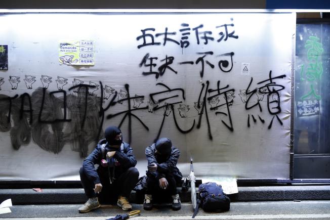 香港民間人權陣線8日發起「一二八國際人權日」大遊行,自中午開始進行到晚上。圖為示威者在貼出的標語下休息。(美聯社)