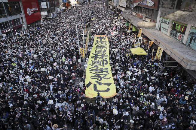 香港民間人權陣線8日發起「一二八國際人權日」大遊行,自中午開始進行到晚上,圖為支持者拉出大幅口號「市民蒙面林鄭蒙心」。(美聯社)