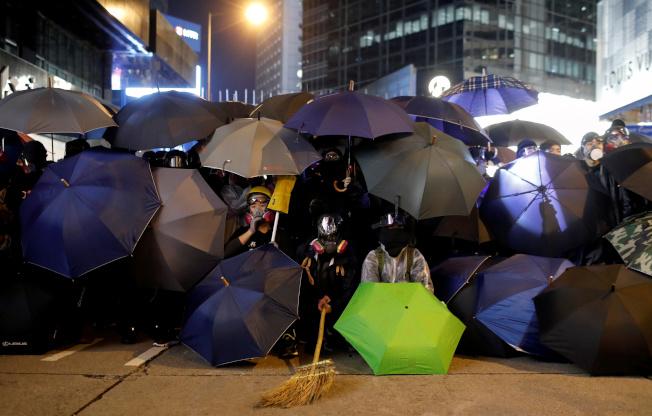 香港民間人權陣線8 日發起「一二八國際人權日」大遊行,自中午開始進行到晚上。圖為示威群眾在街頭躲在雨傘後與警方對峙。(路透)