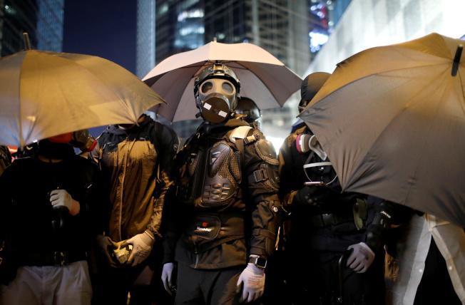 示威群眾躲在雨傘後在街頭與警方對峙。(路透)