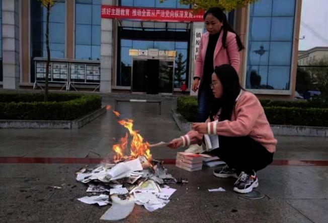 兩名疑似工作人員在圖書館門前焚燒書籍。(取材自紅星新聞)