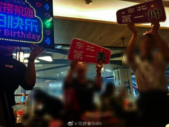 海底撈服務生拿出閃爍著生日快樂的燈牌,齊聚為顧客大唱生日快樂歌。(取材自微博)