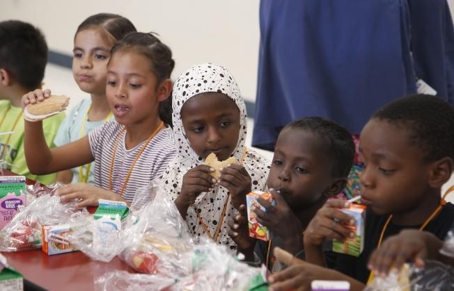 圖為鳳凰城的一所新移民學校,學生正在吃午餐。 (美聯社)