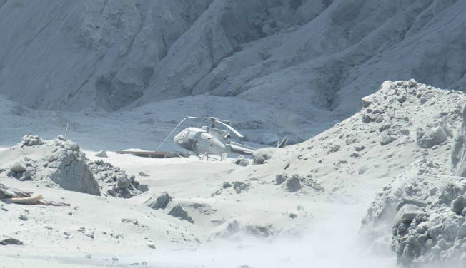 白色火山灰中,可以看到一架被燒焦的直升機殘骸。(取材自推特)