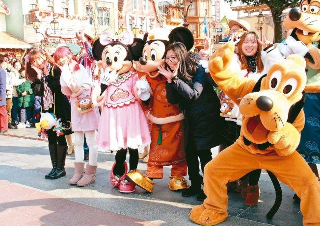 上海迪士尼樂園受遊客歡迎,圖為遊客在上海迪士尼樂園與米奇合影。( 新華社資料照片)