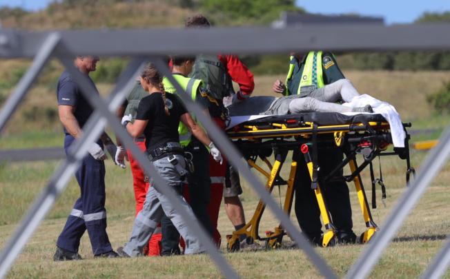 紐西蘭懷特島火山爆發的傷者,9日被送抵紐國北島的華卡塔尼機場,轉送醫院治療。(美聯社)