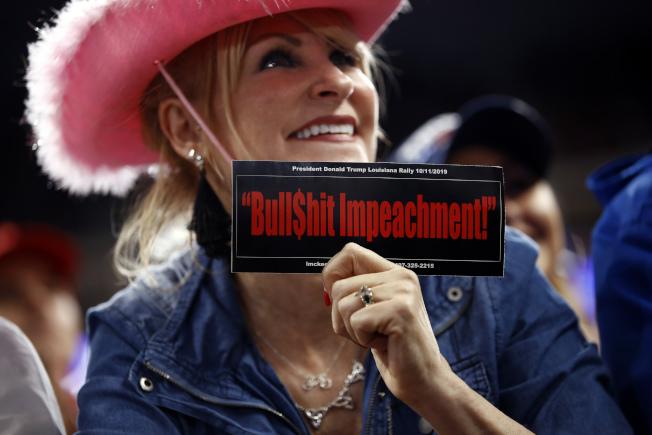 川普的支持者手持的標語牌寫道「狗屁彈劾案」。(美聯社)