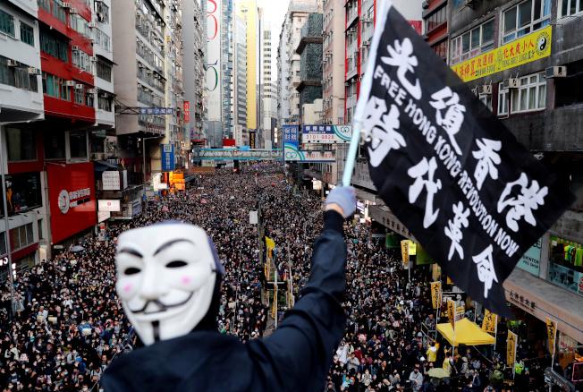 香港浸會大學學生會長方仲賢日前批評台灣民進黨只想用香港人的鮮血,來換取台灣人的選票。圖為香港示威者戴著面具參加人權日遊行。(路透)