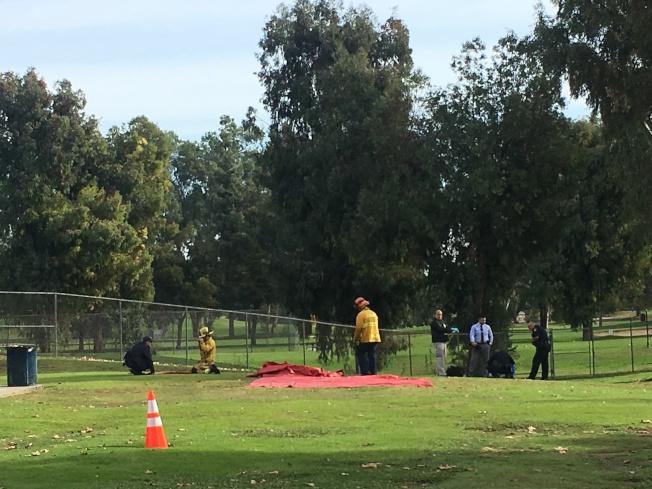警消人員在現場調查,疑為受害人家屬坐在草地上痛哭