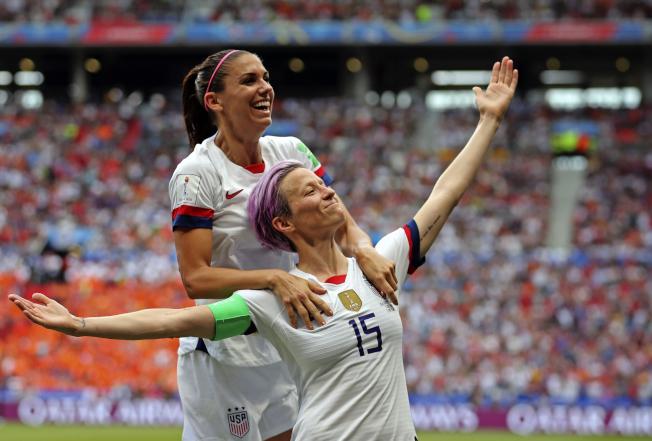 美國女足隊榮膺時代雜誌「年度運動員」。圖為美國女足隊長拉皮諾(前)與明星前鋒摩根在世界盃女足賽場上接受觀眾歡呼。(美聯社)