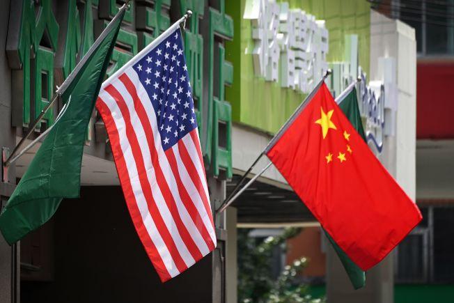 美中談妥第一階段貿易協議,雙方劍拔弩張情勢得以緩和,圖為北京一家旅館門口掛出的美中兩國國旗。(Getty Images)