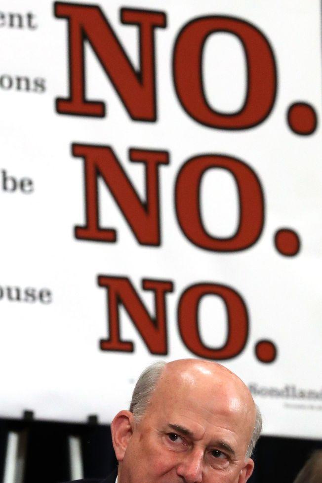 共和黨籍議員高默特坐在一幅標語前,上面有三個「不」字。(Getty Images)