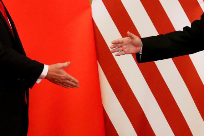 美中已談妥第一階段貿易協議,劍拔弩張態勢即將緩和。圖為美國總統川普訪問北京,向中國國家主席習近平伸手。(路透)