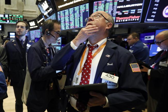 美中貿易談判的進度牽動華爾街股市,圖為紐約證交所交易員注視大盤。(美聯社)