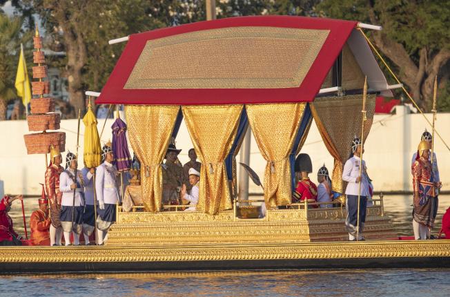 泰國12日舉行王船遊行,做為泰王加冕儀式的最後一道程序。圖為泰王瓦吉拉隆功和王后蘇堤達搭乘的金鴻王船,行駛在昭披耶河上。(美聯社)