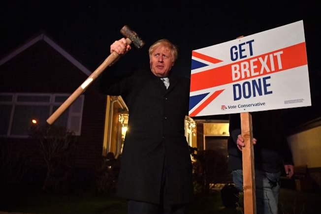 英國大選揭曉,主張脫歐的首相強生大勝,圖為強生在投票前夕手執鐵槌,要求選民支持他完成脫歐大業。(Getty Images)