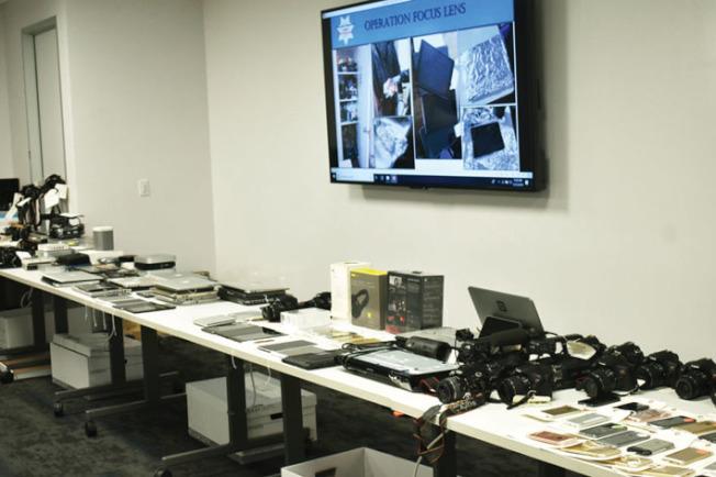 部分被繳獲的相機、手機、筆記本電腦及其它電子產品在記者會上得到公開展示。(記者黃少華/攝影)