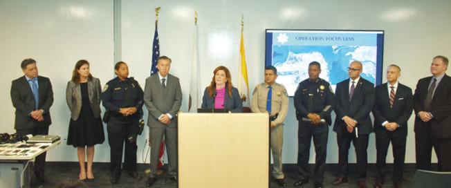 舊金山代理地方檢察長樂素詩(左五)聯同其它多個部門的負責人聯合宣布執法成果。(記者黃少華/攝影)
