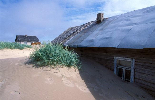 因為沙子堆積很高,且瞬息萬變,因此居民晚上睡覺時都不敢關門,甚至會在屋頂設計逃生窗。 圖擷自Russia Beyond
