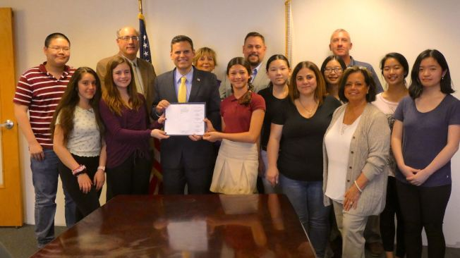 今年5月摩頓市長柯廷森簽署法案,限制使用一次性塑膠袋。圖為柯廷森邀請提出建議的學生們見證法案簽署。(取自摩頓市府官網)
