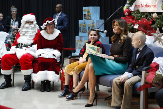 川普總統嘲諷環保少女童貝里獲選為時代雜誌年度風雲人物,第一夫人梅蘭妮亞(右二)似乎有意替丈夫緩頰。圖為她上周到醫院探視病童,讀故事給院童聽。(美聯社)