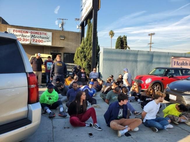 節綠大麻藥房一群店員被銬住在店外席地而坐。(美聯社/加州消保局提供)