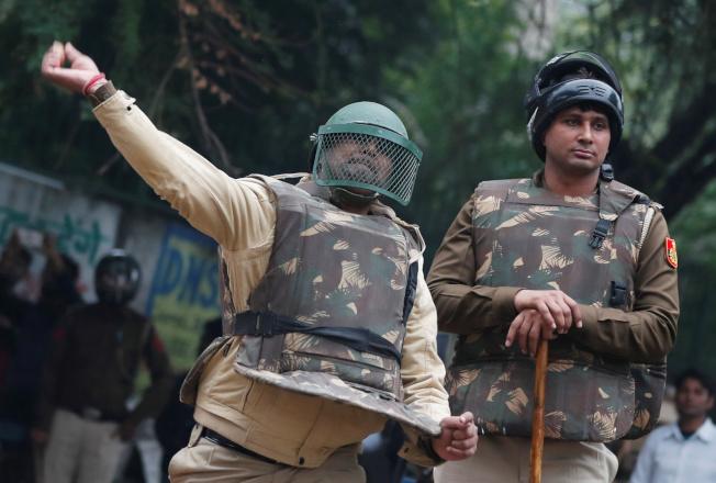 印度東北地區民眾示威,一名警察向抗議者投擲石塊。(路透)