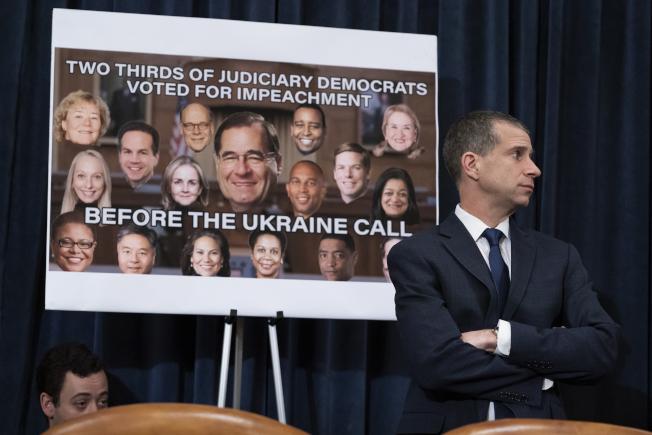 共和黨律師卡斯特在眾院等待司法委員會投票,他身後的看板寫著「司法委員會三分之二的民主黨議員,在電話門之前就已投票支持彈劾。」(美聯社)
