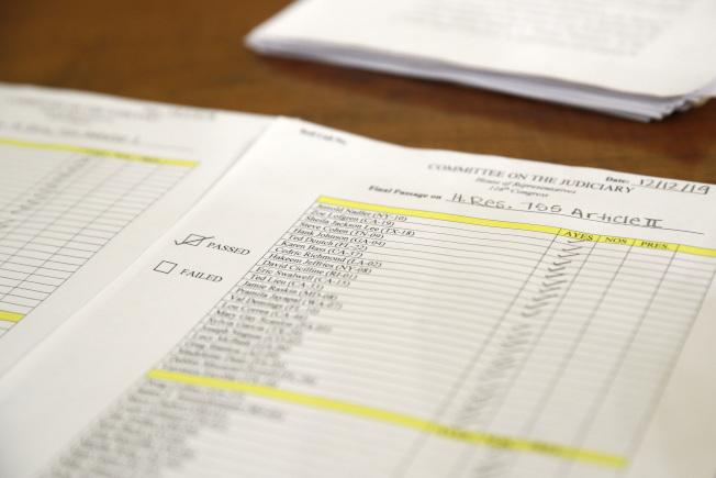 國會眾院司法委員會13日唱名表決,通過彈劾川普總統兩項罪狀。圖為國會職員逐一記錄議員的投票結果。(美聯社)