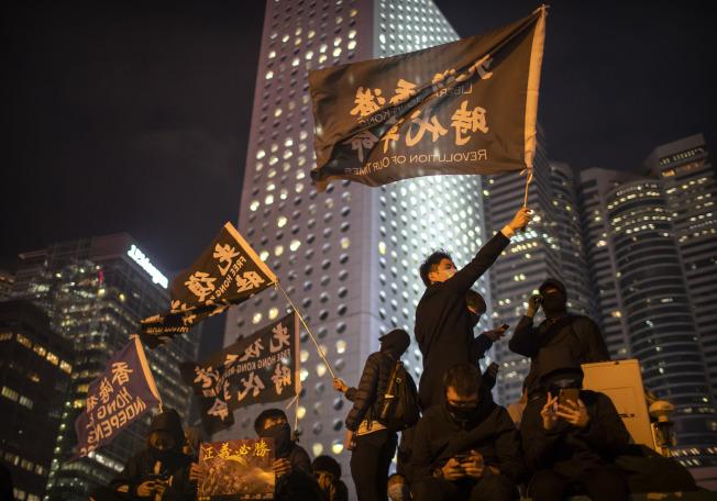 香港示威者13日揮舞著「光復香港,時代革命」旗幟。(美聯社)