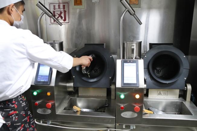 一個工作人員同時操作兩台機器人炒菜機。(取材自觀察者網)