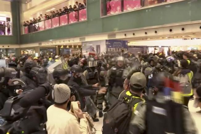 香港反送中示威持續。港民15日在多區商場發動示威活動,防暴警察進入沙田新城市廣場拘捕示威者。 (美聯社)   Hong Kong Protest In this image made from video, police and protester scuffle at a shopping mall in Sha Tin district in Hong Kong, with shoppers watch from balconies above, Sunday, Dec. 15, 2019.  The rally, which had a Christmas shopping theme, was the latest in a series of demonstrations, which have beset Hong Kong for more than six months.(AP Photo)
