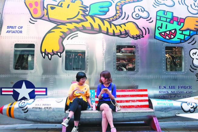 中美貿易談判牽動全球經濟走向,在雙方宣布達成第一階段貿易協議,美方暫停加稅後,北京15日也跟進,暫不對美國商品加稅。圖為北京年輕人坐在塗有美國星條旗的飛彈造型長椅上。(歐新社)