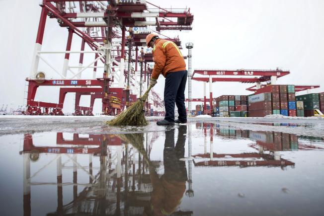 美中達成第一階段貿易協議,專家認為美國什麼也沒撈到。圖為碼頭工作人員在青島港靜靜掃雪。(美聯社)