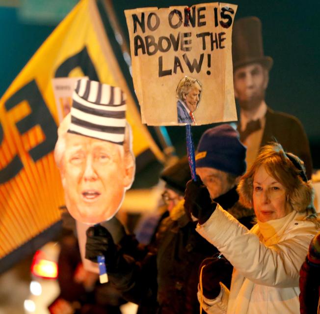 由民主黨主導的支持彈劾川普總統行動,17日傍晚在全美各地展開,各州選民手持標語「無人能凌駕法律之上」,支持眾院18日投票彈劾川普。(美聯社)
