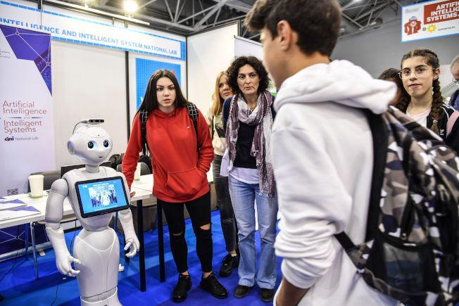 「LinkedIn」公布2019年的「新興工作」名單,自2015年以來雇用率最高的職缺,第一名為人工智慧專家。圖為一群學生與機器人互動。(Getty Images)