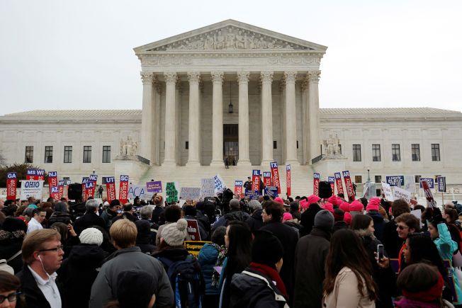 聯邦法官裁決,歐記健保強制每個人都要投保,這種強制規定違憲。圖為支持歐記健保的示威者在華府最高法院前示威。(路透)