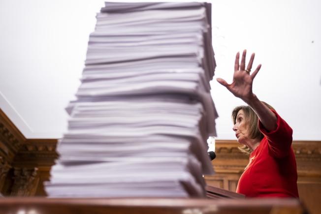 國會眾院議長波洛西說,她要等到參院排出審理議程後,才會提交彈劾案。她身旁的是一疊參院待審法案。(歐新社)