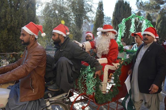 坐在後面的耶誕老人說,「嘿!年輕人你可騎慢一點,安全第一!」(Getty Images)