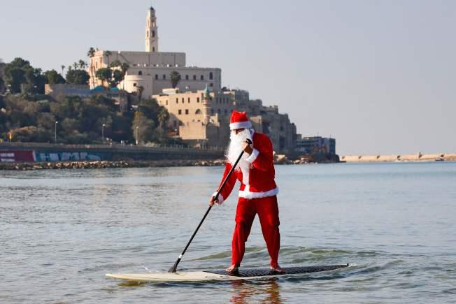 在以色列則有救生員一身耶誕裝扮,划著SUP在特拉維夫海岸邊慢慢前進。(Getty Images)
